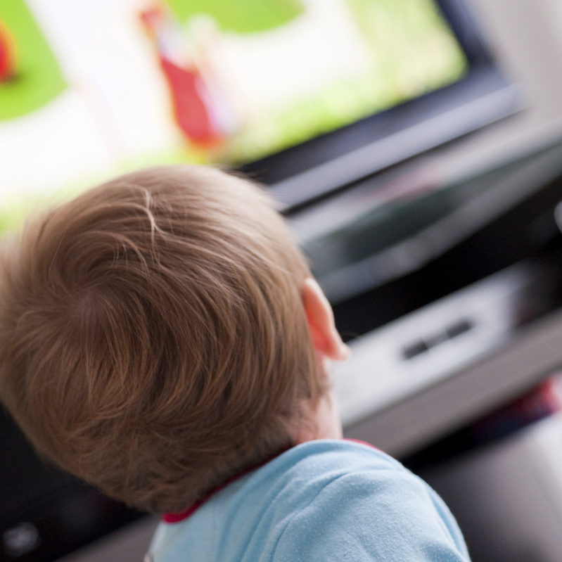 Child in foreground with TV in background