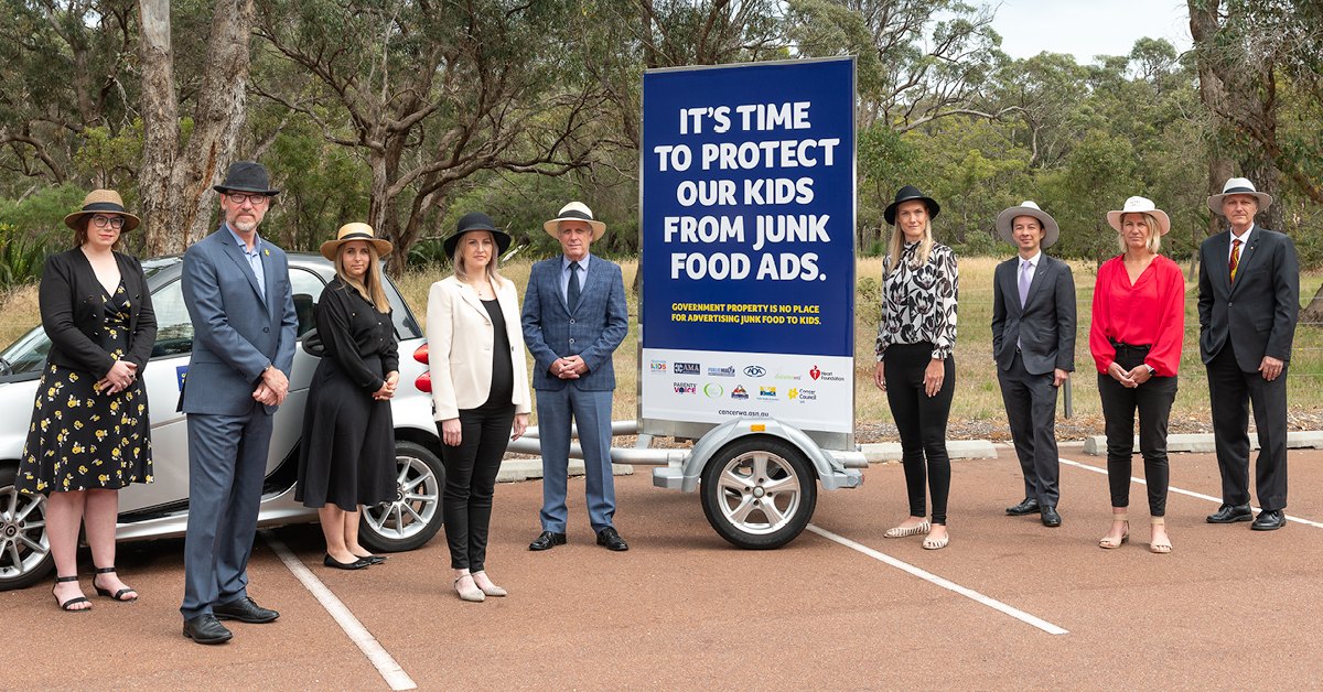 Health Promotion leaders stand next to a health promotion campaign billboard