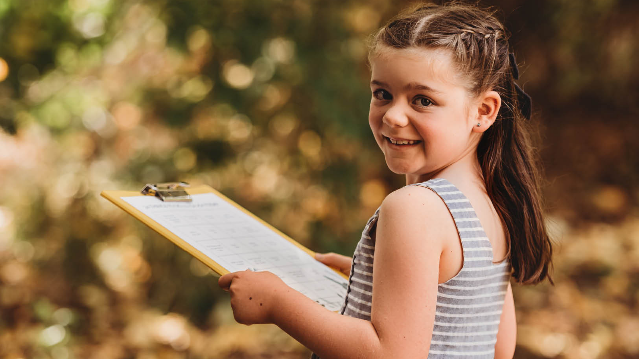Girl in nature looking at the 24 Nature Play Activities list and smiling